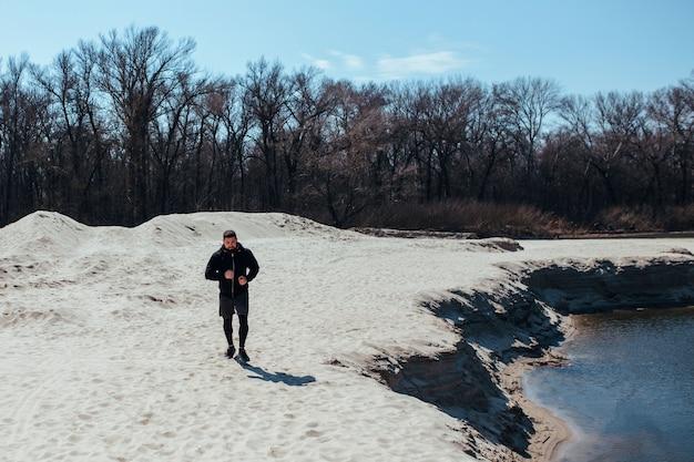 Mannelijke loper oefent op het zand natuur jogging concept