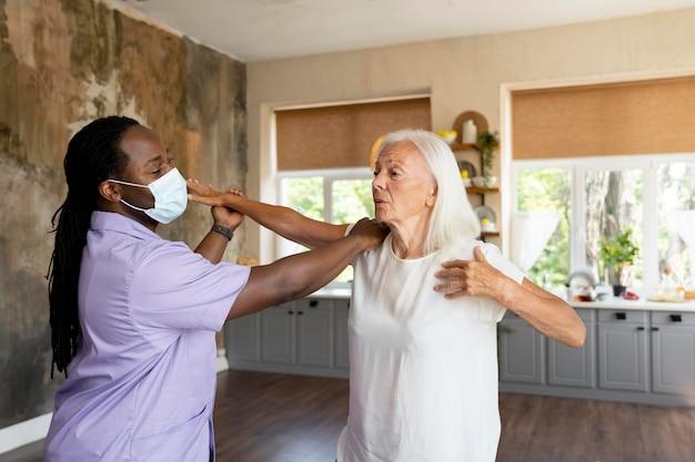 Mannelijke maatschappelijk werker die voor een oude vrouw zorgt