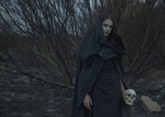 Mannelijke magiër in zwarte kleding met de herfsttakken