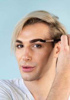 Mannelijke make-up kijkt met zijn wenkbrauwborstel