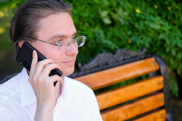 Mannelijke manager, freelancer, zakenman met bril praten op een mobiele telefoon, glimlachend