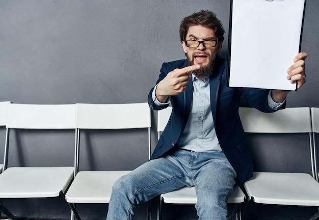 Mannelijke manager zittend op een stoel hervatten baan kopieerruimte