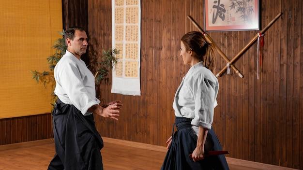 Mannelijke martial arts-instructeur in de oefenzaal die met vrouwelijke stagiair oefent