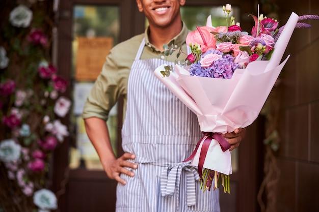 Mannelijke medewerker staat bij de winkeldrempel met een bos bloemen en houdt zijn hand op de heup