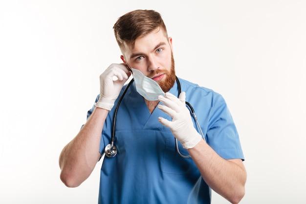 Mannelijke medische assistent met stethoscoop die zijn masker opstijgt