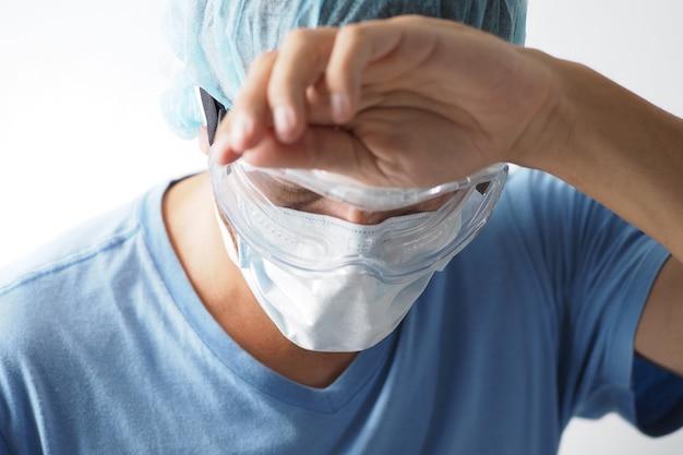 Mannelijke medische werknemer moe en het dragen van beschermende gezichtsmasker en bril