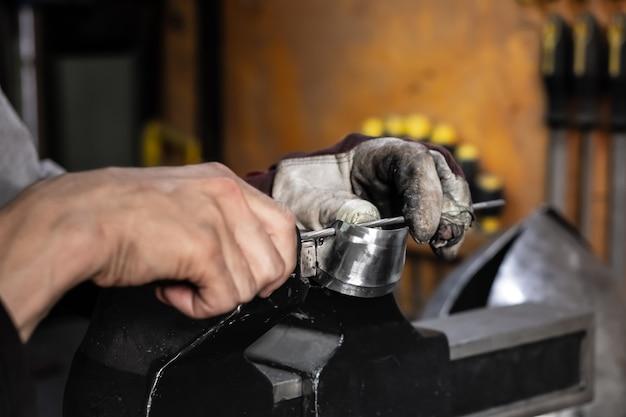Mannelijke metaalarbeider die stuk van metaalassemblage construeert of herstelt. man handen werken met metalen onderdelen in een werkplaats