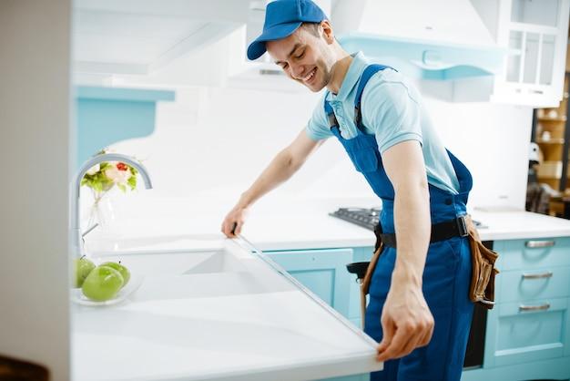 Mannelijke meubelmaker in uniform meet tafelblad in de keuken. klusjesman die garnituur installeert, service aan huis repareert