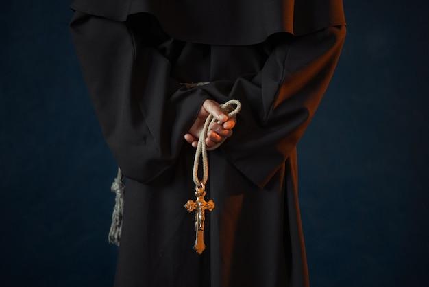 Mannelijke monnik in zwart gewaad houdt houten rozenkrans en kruis in handen, religie. mysterieuze monnik in donkere cape