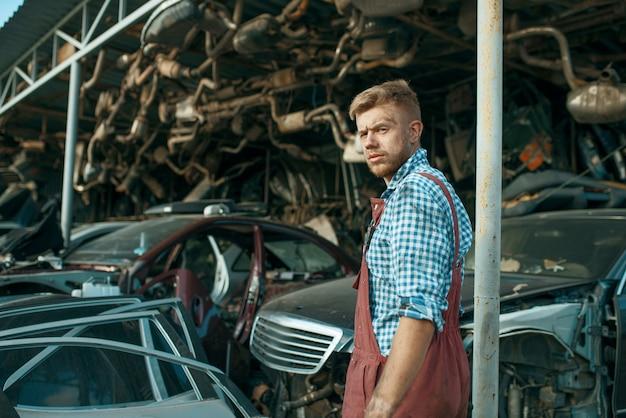 Mannelijke monteur bij de stapel auto's op autokerkhof. autoschroot, autoafval, auto-afval. beschadigd en verpletterd transport, sloperij