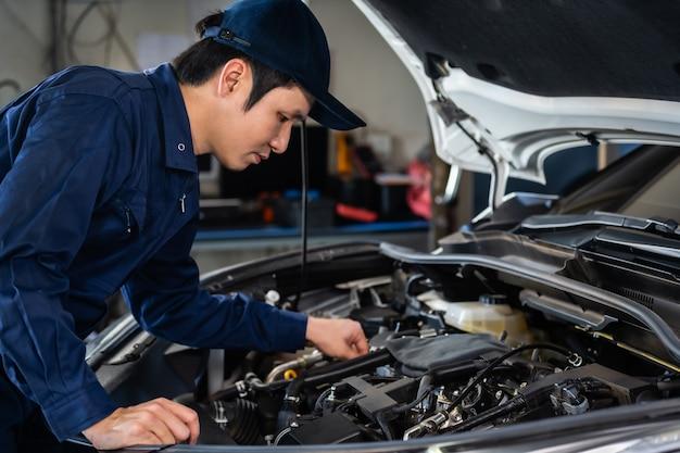 Mannelijke monteur controleren en repareren van motor, auto service