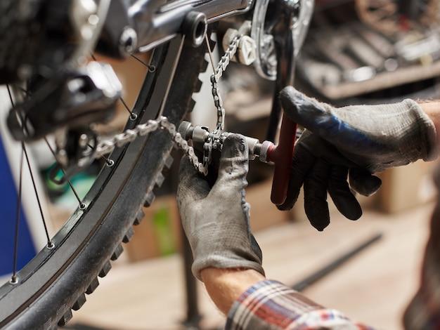 Mannelijke monteur die service maakt in de fietsreparatiewerkplaats met behulp van gereedschap