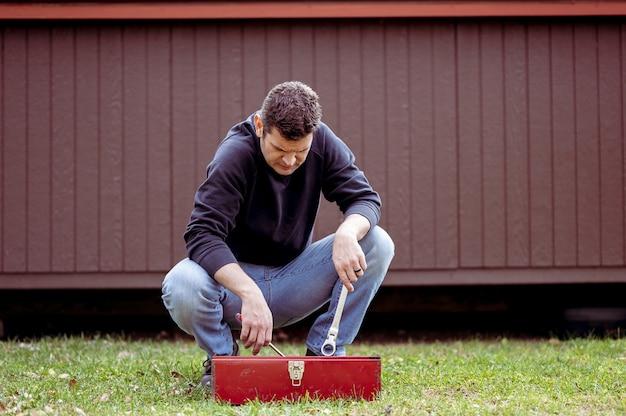 Mannelijke monteur die wat gereedschap van een gereedschap grijpt