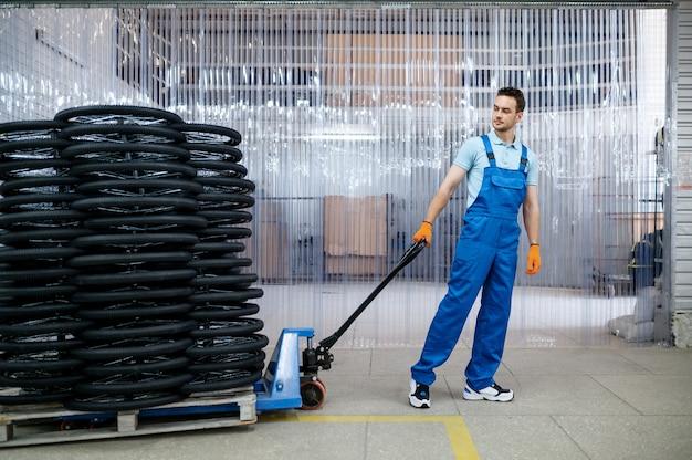 Mannelijke monteur draagt fietswielen op een kar in de fabriek. de assemblagelijn van fietsvelgen in de werkplaats, installatie van fietsonderdelen, moderne technologie