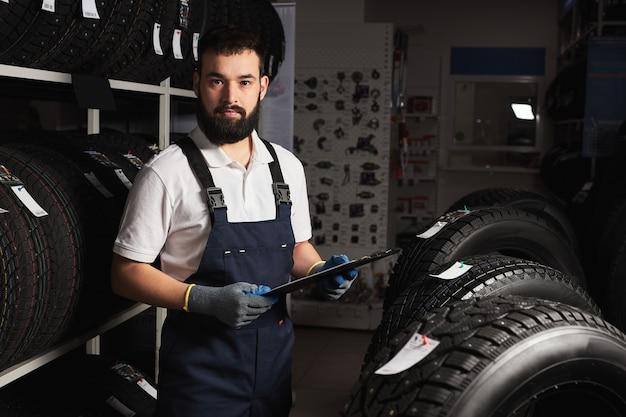 Mannelijke monteur in de buurt van rek met autobanden in auto winkel, camera kijken, klaar om te helpen met keuze, klanten en klanten bedienen, uniform dragen