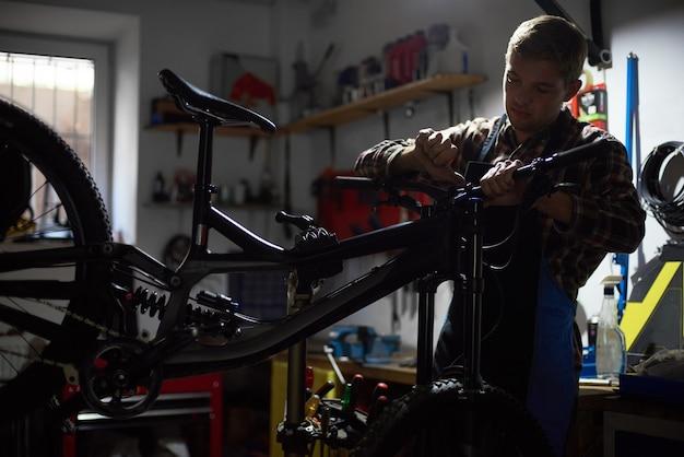 Mannelijke monteur service maken in fietsenmaker met gereedschap