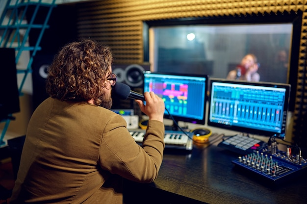 Mannelijke muzikant en vrouwelijke artiest, opnamestudio interieur op de achtergrond. synthesizer en audiomixer, muzikantenwerkplek, creatief proces