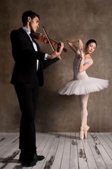 Mannelijke muzikant met viool en ballerina in tutu jurk