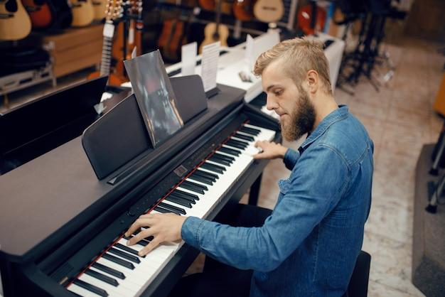 Mannelijke muzikant probeert te spelen op piano in muziekwinkel. assortiment in muziekinstrumentenwinkel, toetsenist die apparatuur koopt, pianist op de markt