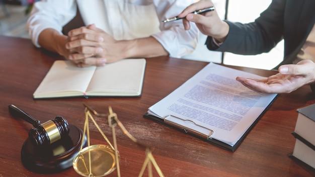 Mannelijke notarisadvocaat of rechter raadpleegt of bespreekt contractpapieren met zakenmancliënt