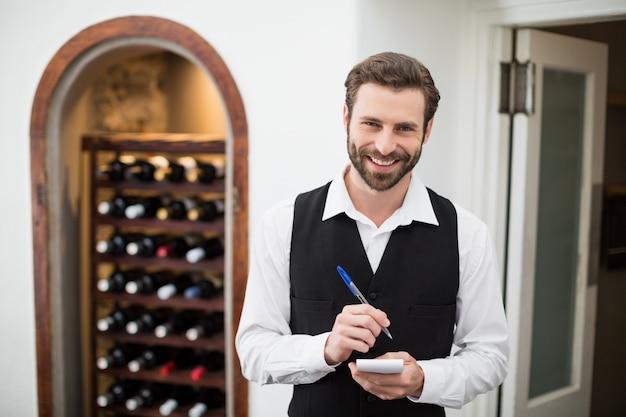 Mannelijke ober die terwijl het nemen van orde glimlacht