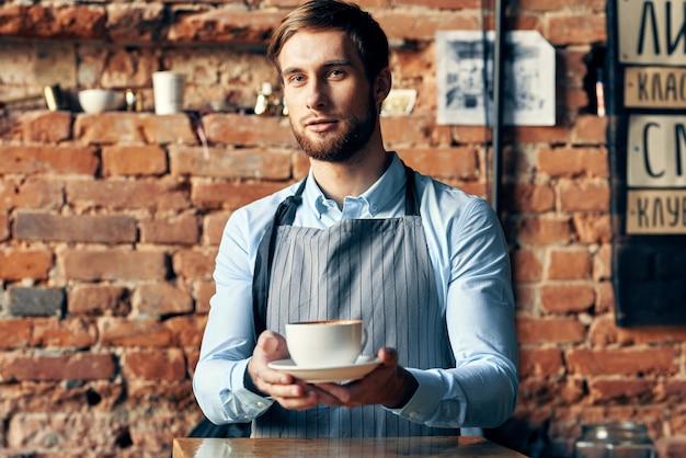 Mannelijke ober schort koffiekopje professionele barista werkista