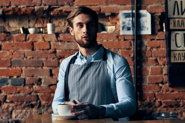 Mannelijke ober schort service koffiekopje baksteen