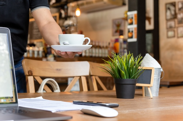 Mannelijke ober serveert koffie met laptop en bril op werktafel in café.
