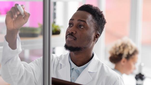 Mannelijke onderzoeker met tablet in het laboratorium voor biotechnologie