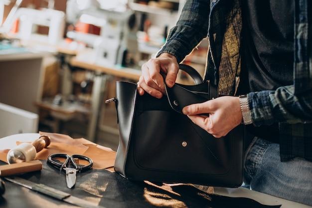 Mannelijke ontwerper en lederen kleermaker werken in een fabriek close-up