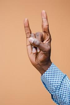 Mannelijke opgeheven mensenhand tonend een teken van de zwaar metaalrot, hoornengebaar
