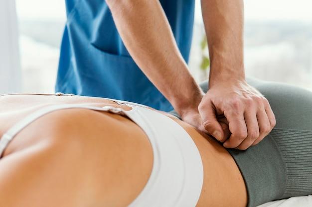 Mannelijke osteopaat die de onderrug van de vrouwelijke patiënt controleert