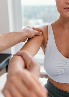 Mannelijke osteopaat die de schouder van de vrouwelijke patiënt controleert