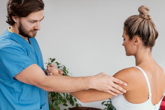 Mannelijke osteopaat die de schouderbeweging van de vrouwelijke patiënt controleert