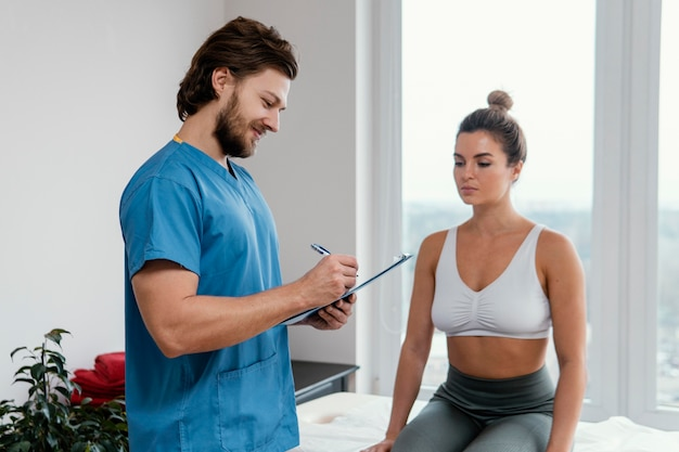 Mannelijke osteopaat therapeut met vrouwelijke patiënt klembord ondertekenen in het kantoor