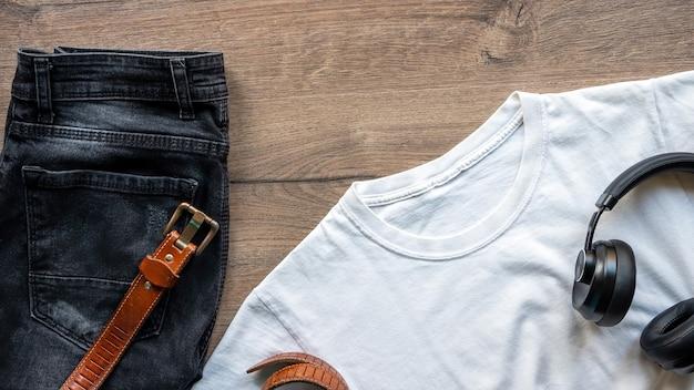 Mannelijke outfit kleren op tafel, t-shirt, spijkerbroek, verwarmingstoestellen en een riem. bovenaanzicht