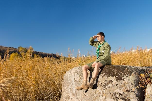 Mannelijke padvinder zittend op enorme rots die het brede landschap op het kampterrein met hoge bruine grassen onderzoekt.