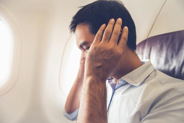 Mannelijke passagier die oorpop op het vliegtuig heeft