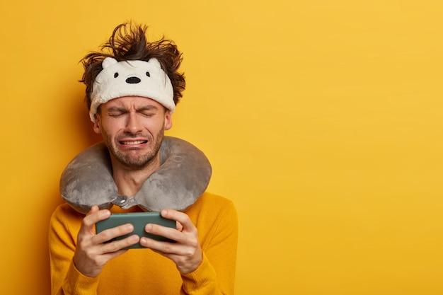 Mannelijke passagier draagt een opgeblazen reiskussen over de nek en een schattig oogmasker
