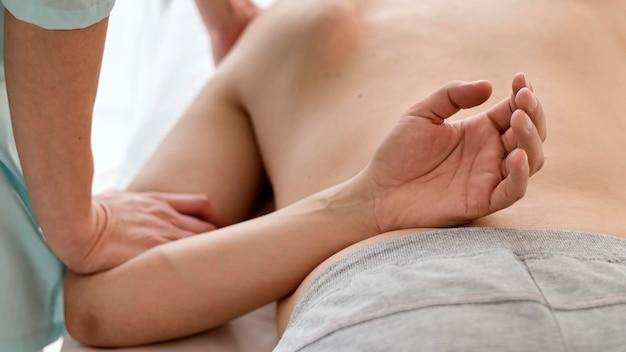 Mannelijke patiënt die therapie met fysioloog ondergaat