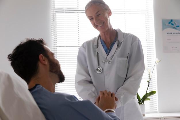 Mannelijke patiënt in bed praten met een verpleegster