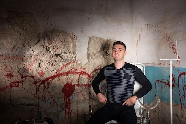 Mannelijke patiënt in kerker met bloedige muren in een halloween-horrorconcept