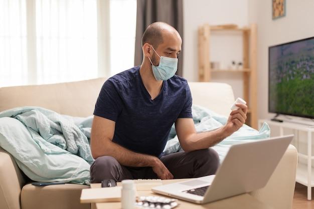 Mannelijke patiënt in quarantaine op tijd op zoek naar medisch advies online.