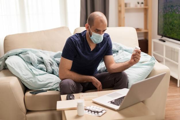 Mannelijke patiënt met pillenfles die naar laptop kijkt tijdens zelfisolatie.