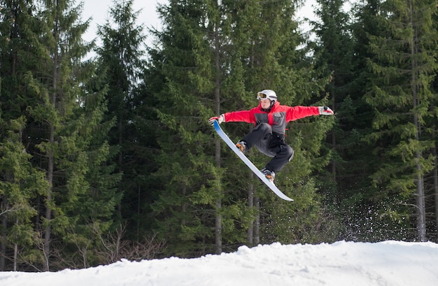 Mannelijke pensionair op snowboard die over de helling springt