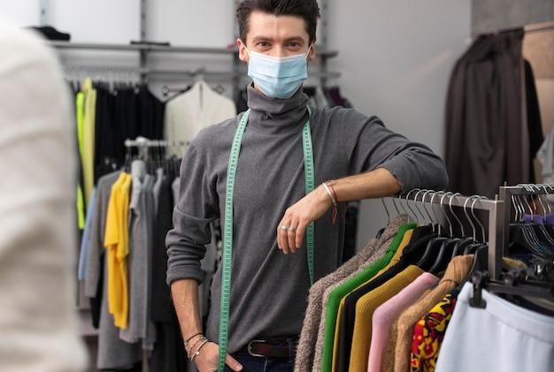 Mannelijke personal shopper met masker werken