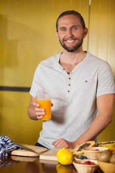 Mannelijke personeel sinaasappelsap glas houden bij biologische sectie