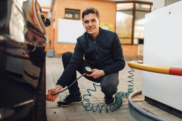 Mannelijke persoon controleert de bandenspanning