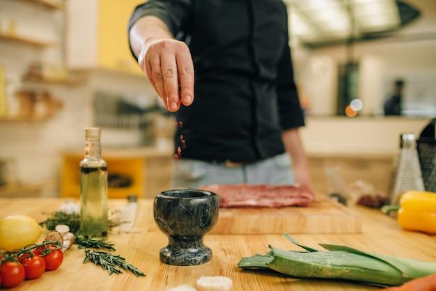 Mannelijke persoon die rauw vlees op een houten bord marineert. chef-kok kokende ossenhaas met groenten, kruiden en specerijen