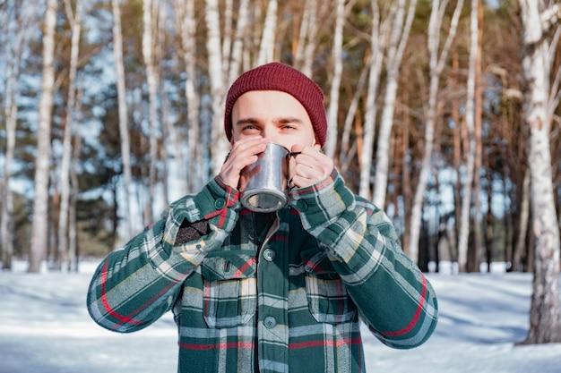 Mannelijke persoon drinkt uit een beker in een besneeuwde winter bos. de mens in geruit overhemd houdt in openlucht kop van koffie
